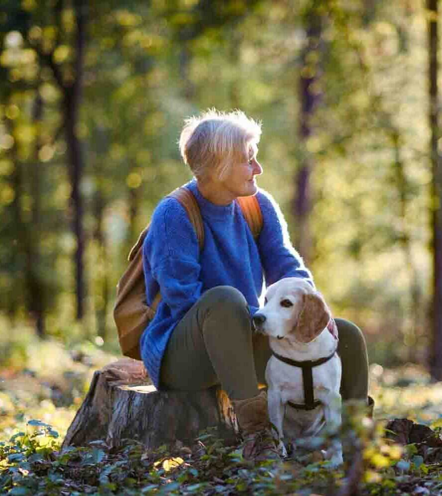 a senior woman hiking with her dog